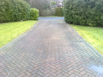 a stained dirty block paved drive before cleaning